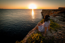 Faceless Woman Resting On Cliff During Scenic Sunset