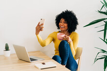 Cheerful Black Woman Making Video Call On Smartphone At Table