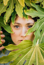 Calm Woman Standing Behind Green Foliage
