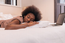Young Ethnic Woman Sleeping On Bed Near Opened Laptop