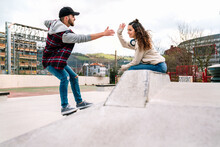 Man Giving Five To Woman While Practicing On Freeline Skates