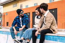 Young Students Talking And Smiling On Urban Parapet
