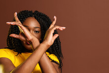 Black Woman Covering Face With Crossed Arms