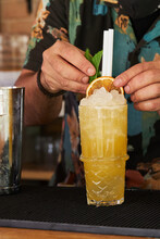 Crop Barman Adding Dried Citrus And Mint To Cocktail