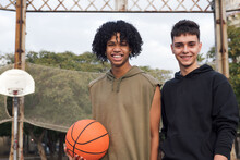 Smiling Multiracial Friends Standing Near Net With Basketball