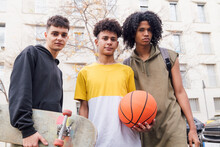 Multiracial Young Friends Standing With Ball And Skateboard