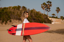Sportswoman With Surfboard On Shore Against Trees