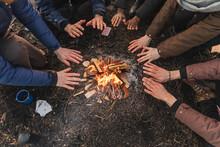Multiethnic Friends Warming Hands By Fire