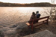 Men Sitting On Bench Near Pond At Sunset