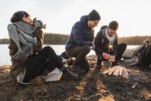 Positive Multiethnic Campers Lighting Fire On Lake Coast