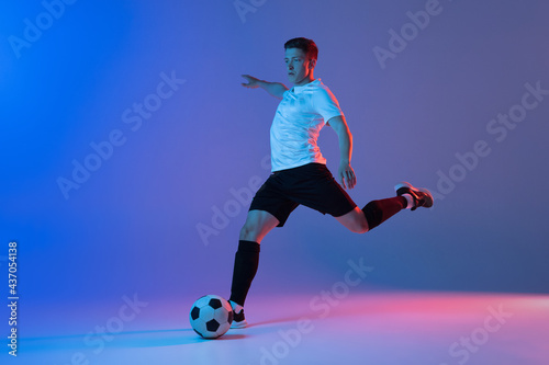 Fototapeta premium Young Caucasian man, male soccer football player training isolated on gradient blue pink background in neon light