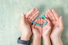 Top View On Kid Hands Holding Rosary Beads In Father's Hands. Ramadan Kareem Background. Muslim Man And Child Holds A Rosary. Flat Lay.
