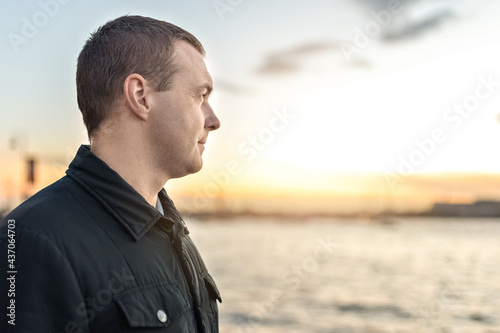 Carta da parati Portrait of a young man watching the sunset on the embankment of the river in th