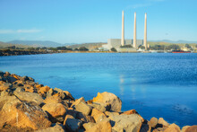 Rocky Beach And An Old Power Plants At Whose Three Large Smokestacks Can Be Seen From Anywhere In Morro Bay. Morro Bay State Park, California Central Coast