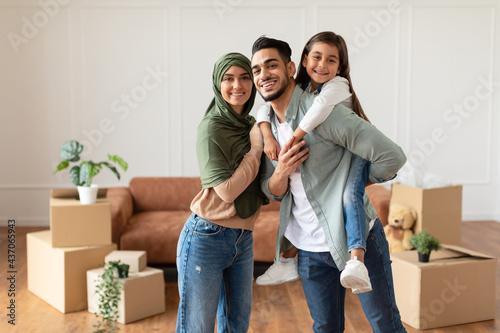Fototapeta Happy muslim family looking at camera, posing on moving day