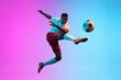 Leinwandbild Motiv One African man, professional soccer football player training isolated on gradient blue pink background in neon light.