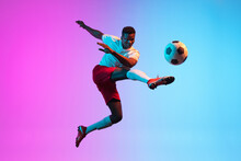 One African Man, Professional Soccer Football Player Training Isolated On Gradient Blue Pink Background In Neon Light.