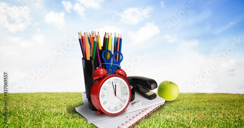 Composition of coloured pencils, sationery and apple with alarm clock, in sunny field with blue sky