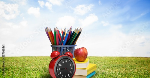 Composition of coloured pencils, books and apple with alarm clock, in sunny field with blue sky