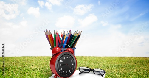 Composition of coloured pencils in pot with glasses and alarm clock, in sunny field with blue sky