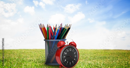 Composition of coloured pencils in pot with alarm clock, in sunny field with blue sky