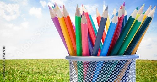 Composition of coloured pencils in mesh metal container, in sunny field with blue sky