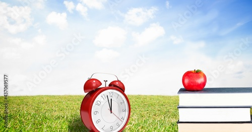 Composition of red retro alarm clock with apple on stack of books over grass
