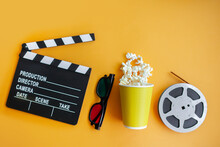 Clapperboard, Cinema Glasses, Film Strip And Popcorn Bucket On Yellow Background. Movie Night Concept. Flatlay. Top View. Copy Space