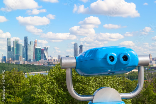 Carta da parati blue stationary binoculars on observation deck with view of spring Moscow river and city on background