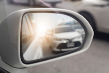 View Of Traffic From Behind Through The Mirrors Wing Of A White Car. With Abstract Of Shining From Behind.