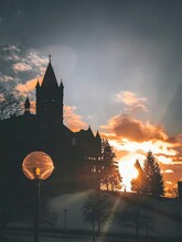 A Church Stands On A Snow-covered Hill, Silhouetted By The Golden Rays Of The Sun Setting Behind It.