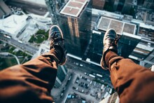 View From The Lap Of A Man Sitting On Top Of A Rooftop With Legs Dangling Over The Edge.