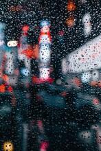 The Lights Of The Urban Center Of A City Viewed Through A Rain-dappled Window.