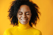 Overjoyed. African American Young Girl Portrait With Closed Eyes,against Yellow Background.