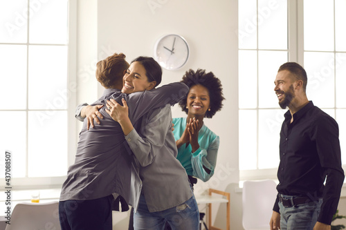 Valokuva Group of positive diverse people hugging their friend or colleague