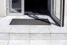 Threshold Made Of Light Gray Ceramic Tiles With Steps At The Entrance To The Store With A Foot Mat And An Open Glass Door At The Facade Of An Office Building Close-up Front View, Nobody.