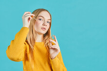 Portrait Of Young Girl Applying Serum On Her Face On Blue Background.