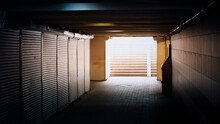 Empty Dark Underpass. Closed Shutters Of Shops And Light At The End Of The Tunnel.