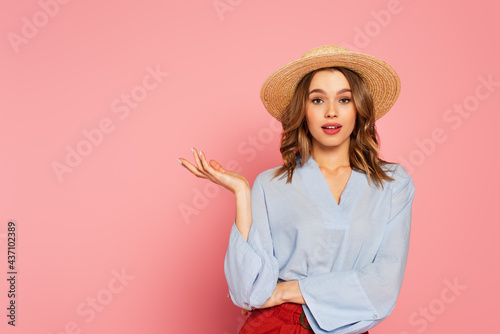 Fotografia Young woman in straw hat looking at camera and pointing with hand on pink backgr