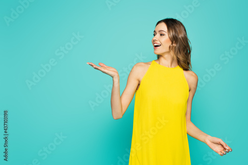 Billede på lærred Cheerful woman in yellow dress pointing with hand isolated on blue