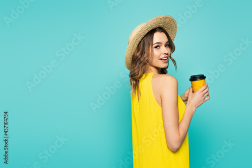 Young woman in dress and sun hat holding paper cup isolated on blue Fototapet