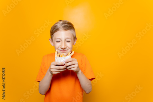 Fotomural a boy in an orange T-shirt holds a bag of deep-fried potatoes in front of him an