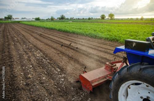 Carta da parati A tractor with a milling machine is cultivating a farm field