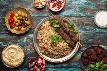 Various Turkish Dishes: Meat Kebab With Tabbouleh Salad, Falafel, Hummus, Olives, Pistachios And Other Middle Eastern Meze On Wooden Table Top View. Ethnic Arab Food, Cuisine Of Turkey