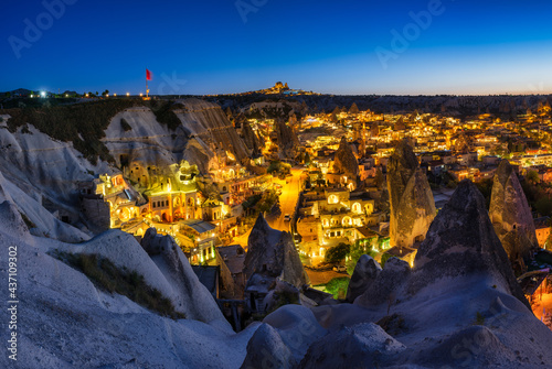 Goreme, Cappadocia, Turkey. View of the evening city from the mountain. Bright evening city and clear sky. Landscape in the summertime. UNESCO heritage. Vacation and tourism. #437109302