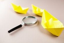 Yellow Paper Boats And A Magnifying Glass