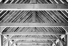Black And White Photo Of The Wood And Metal Framing Of A Small Covered Bridge.  Diagonal And Horizontal Lines