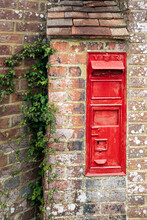Old Disused Typical Red English Postbox On The Wall Of A House