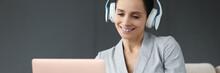 Smiling Woman In Headphones Works Behind Laptop