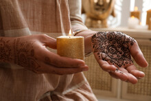 Woman With Henna Tattoo Holding Burning Candle Indoors, Closeup. Traditional Mehndi Ornament